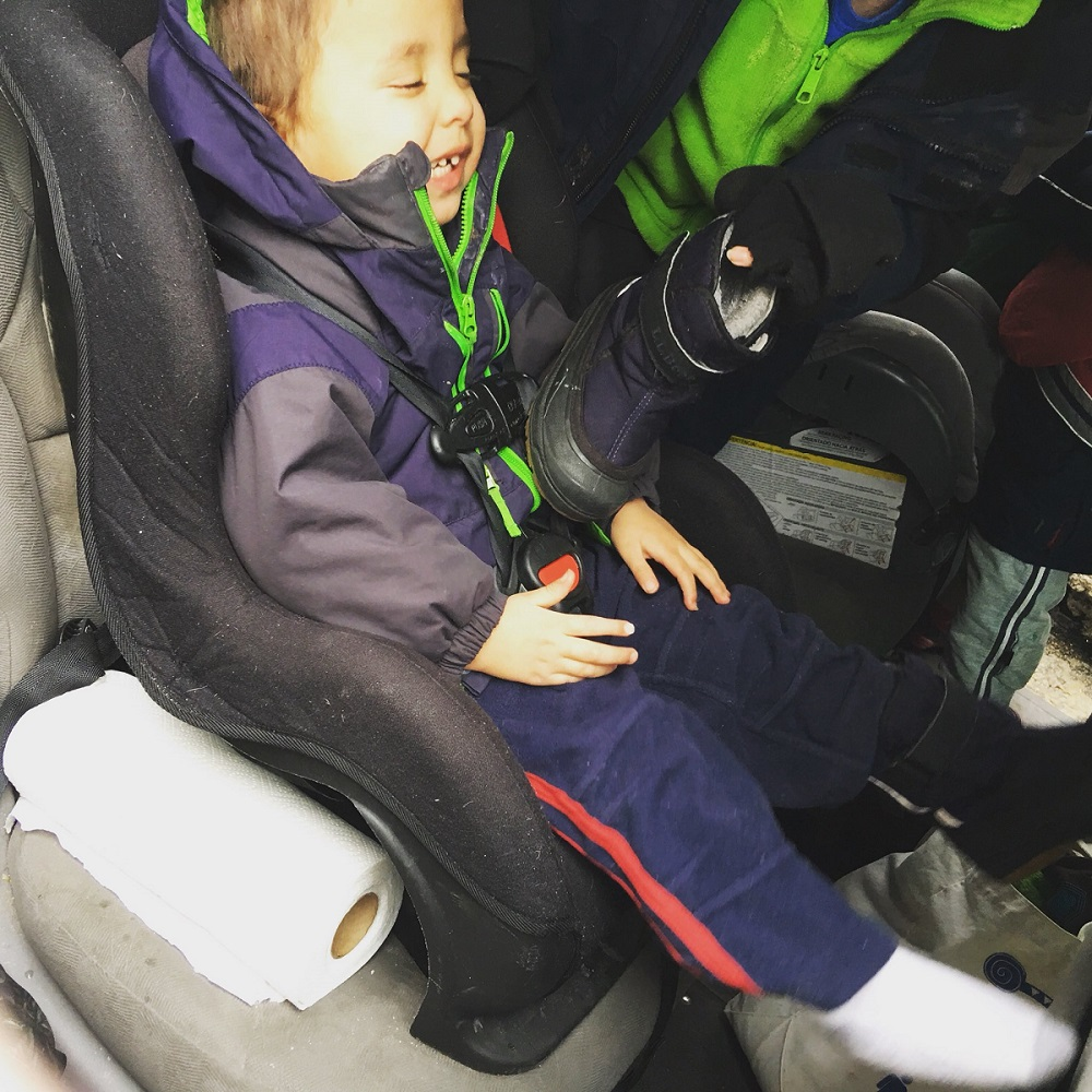 Almost three year old takes his boot off