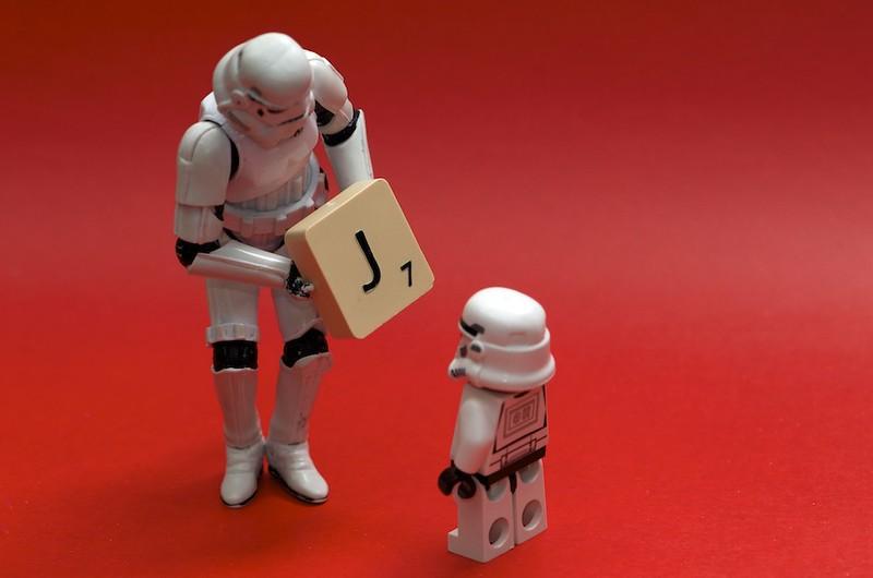 A Star Wars stormtrooper figure hands a Scrabble tile of the letter J to a mini Star Wars stormtrooper figure. (Photo by Kristina Alexanderson via Flickr/Creative Commons https://flic.kr/p/bAoRak)