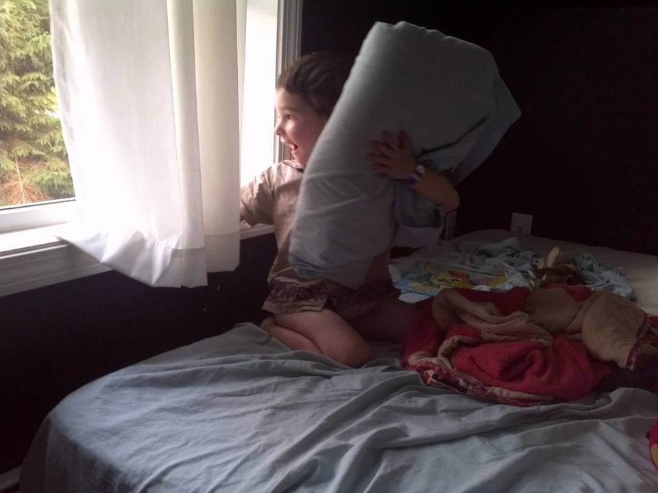 Four year old sits up and looks out the window, with the pillow still on his head.