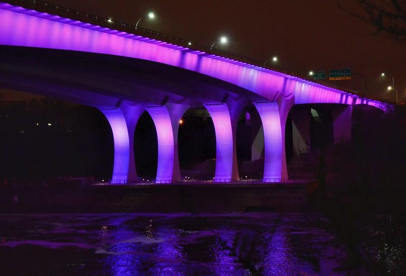 35W bridge in Minneapolis illuminated purple. (Photo by jpellgen via Flickr/Creative Commons https://flic.kr/p/G6fwsf)