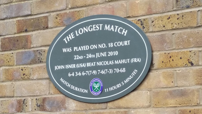 """Sign outside a Wimbledon court says: """"The longest match was played on No. 18 court 22nd - 24th June 2010 John Isner (USA) beat Nicolas Mahut (FRA) 6-4 3-6 6-7 (7-9) 7-6 (7-3) 70-68 Match Duration 11 hours 5 minutes"""" (Photo by Bill Walsh via Flickr/Creative Commons https://flic.kr/p/ye6FAK)"""