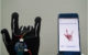 """Smart glove makes sign for """"I love you"""" and screen of smartphone shows the sign and the words """"I love you"""" (photo Jun Chen Lab/UCLA)"""