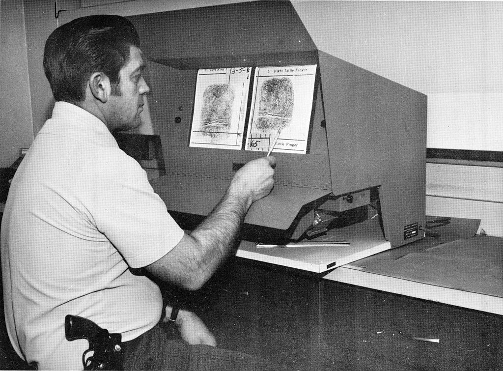 Detective studying fingerprints (Buffalo Police Department via Wikicommons https://commons.wikimedia.org/wiki/File:Buffalo_Police_Department_Annual_Report_1973_-_02.jpg)