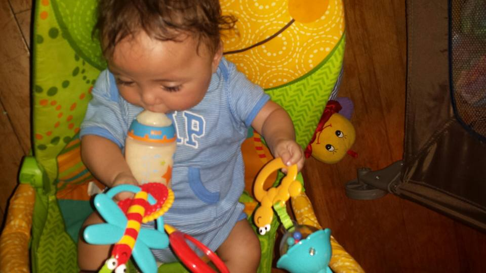 Baby boy is playing with two toys and bouncing in his bouncy chair while also drinking a bottle.