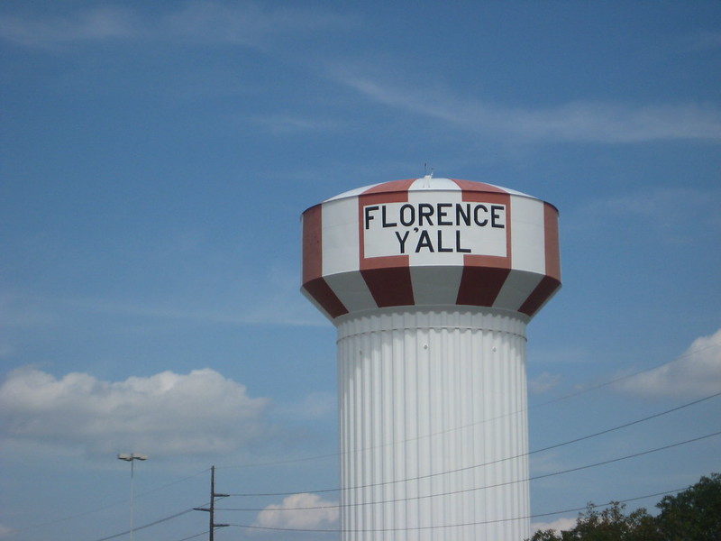"Water tower with red and white vertical stripes and the words ""Florence Y'all"" painted in black block letters. Photo by madaise via Flickr/Creative Commons https://flic.kr/p/5kyS3h"