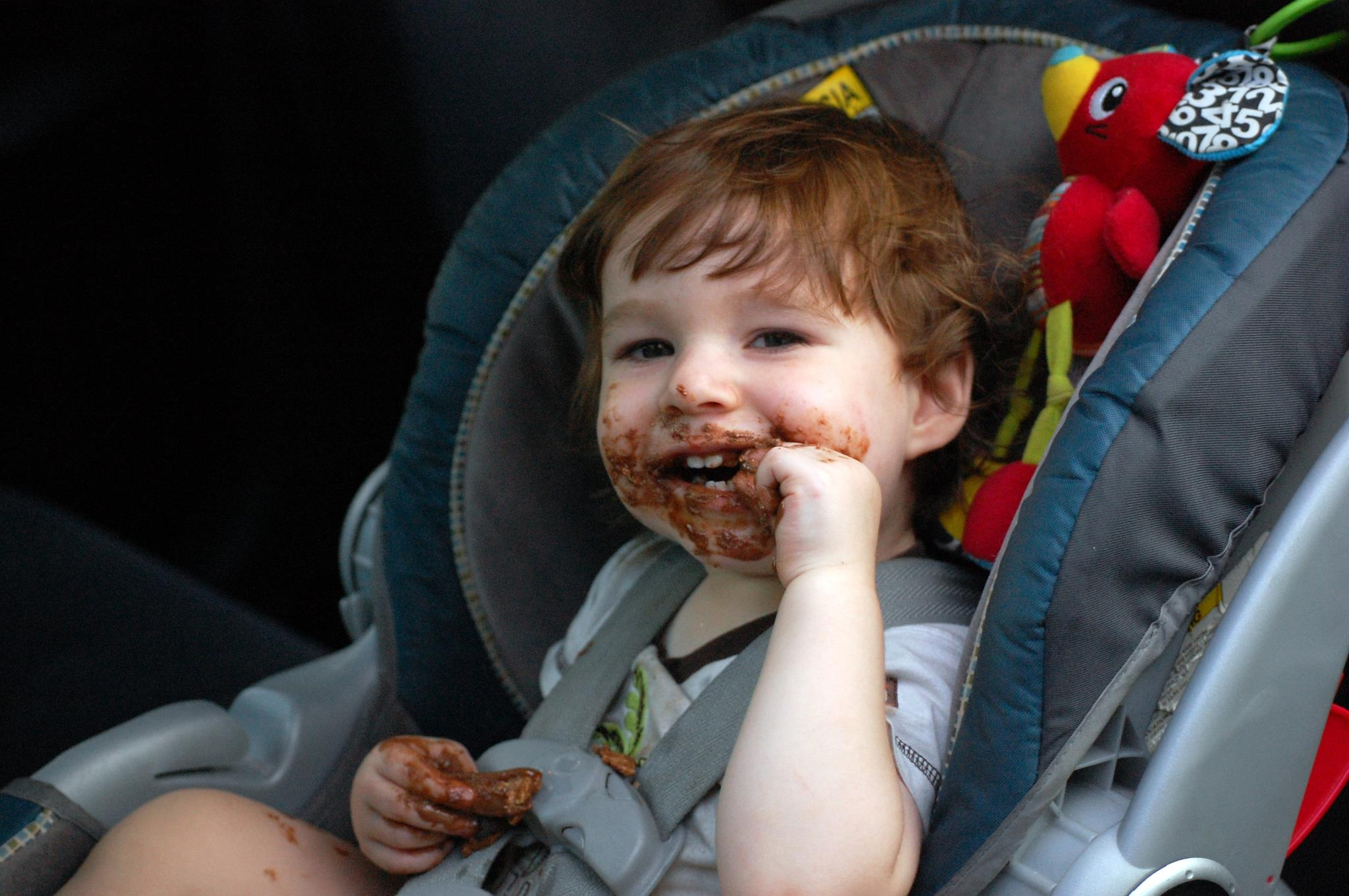 One year old is covered in chocolate and smiling