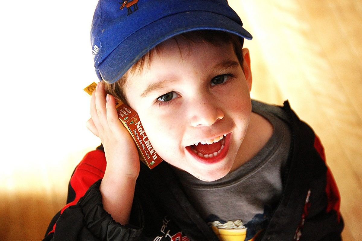 Two year old holds a box of bouillon cubes up to his ear like a phone