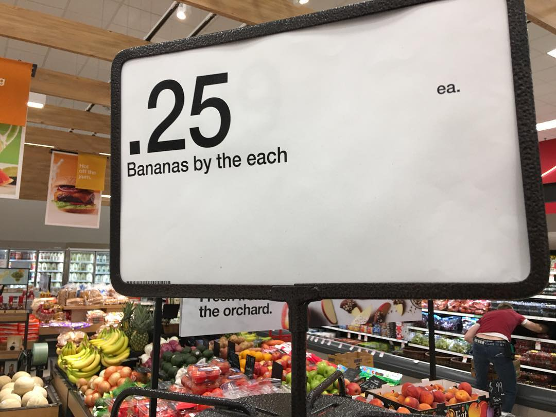 "Sign says ""Bananas by the each"" for 25 cents"