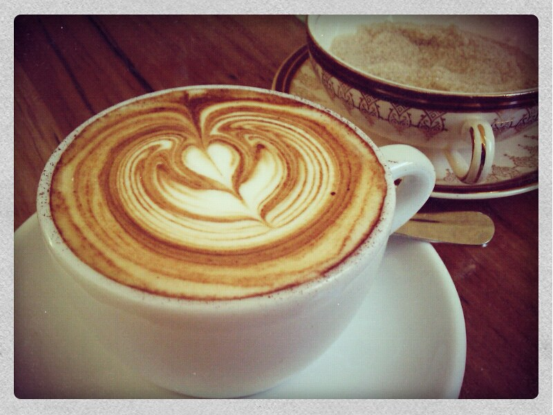 Very elaborate flower design in a large latte in a white cup. (Photo by Cheryl Foong via Flickr/Creative Commons https://flic.kr/p/dz1VFC)