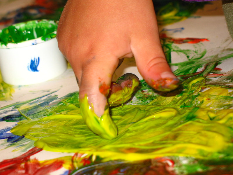 A hand is finger painting, mostly yellow. (Photo by Christine Jackowski via Flickr/Creative Commons https://flic.kr/p/dXbHq)