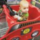 Baby girl drives the fire truck shopping cart
