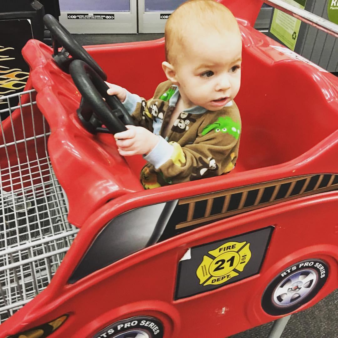 Baby girl drives the fire truck shopping cart