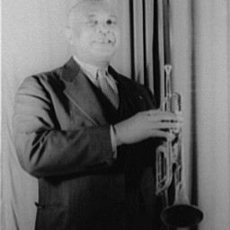 Portrait of W.C. Handy, wearing a suit, holding a trumpet.