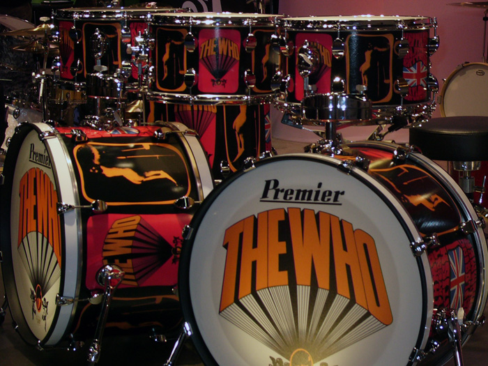 """A replica of Keith Moon's drum set, orange drum shells with white drum heads. The words """"THE WHO"""" are written in orange letters. (Photo by BigDrumThump.com via Flickr/Creative Commons https://flic.kr/p/4GJDSJ)"""