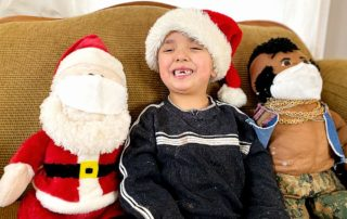 Five year old with Santa and Mr. T (who are wearing masks)