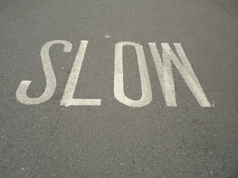 """Slow"" written on pavement (photo by Jerzy Kociatkiewicz via Flickr/CC)"
