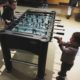 Big bro and little bro playing foosball
