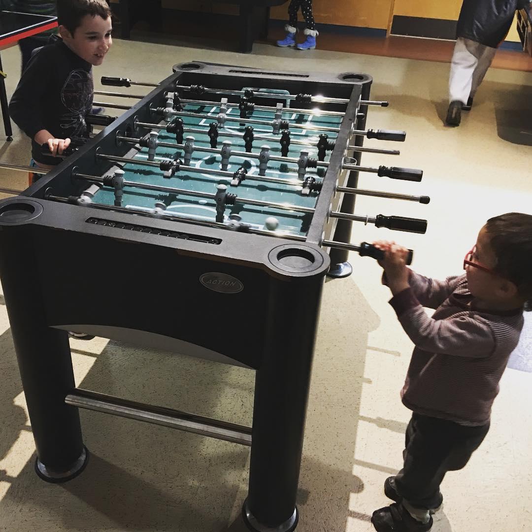 Big bro and little bro playing foosball