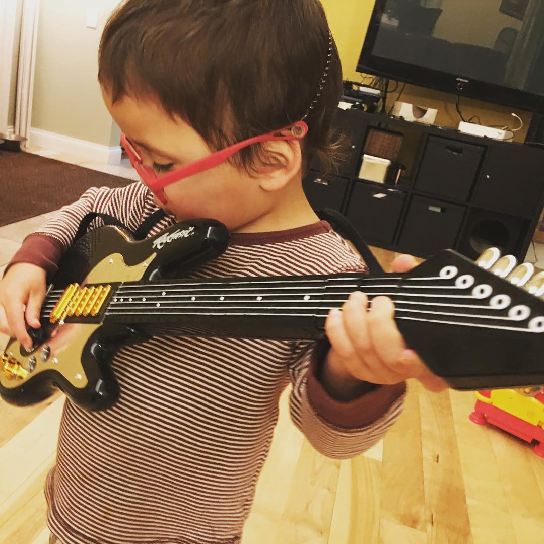 Almost three year old playing a toy guitar