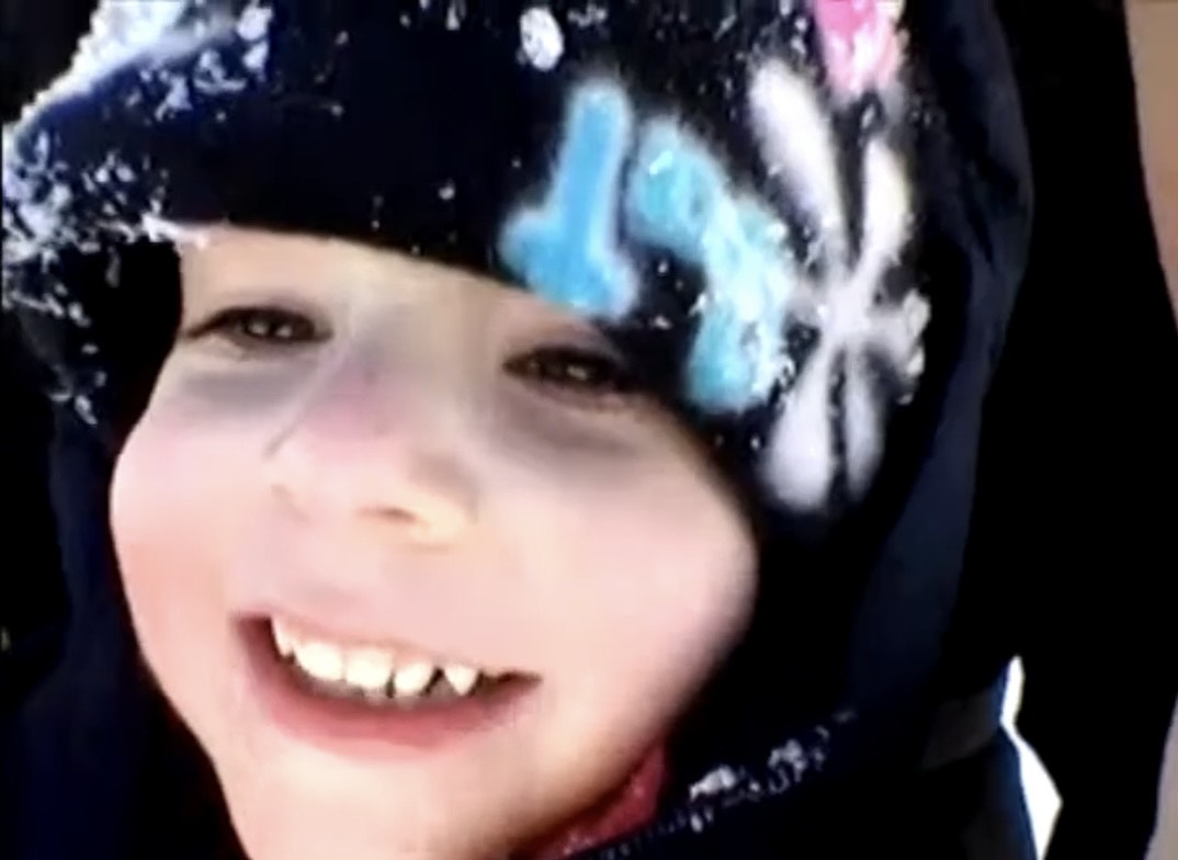 Two year old smiles because he's sledding