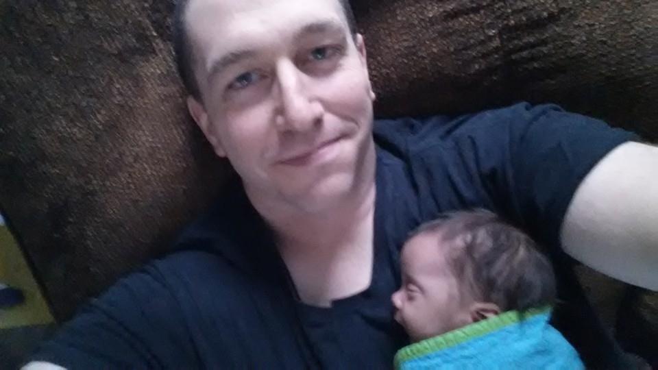 Brady holding newborn baby while he's sleeping. Awww.