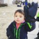 Three year old is wearing a grown-up-sized glove on his left hand and holding it up for the camera