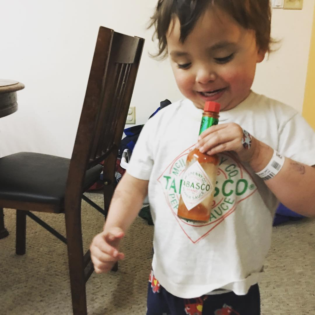 Three year old smiles. He's wearing a t-shirt with the Tabasco sauce logo on it, and he's holding in front of him a bottle of Tabasco sauce with the same logo.