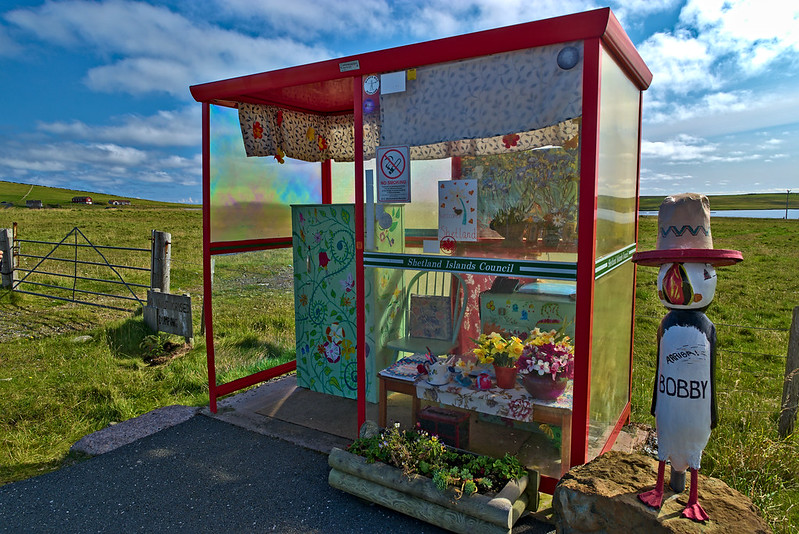 A bus shelter with flowers, art on display and colorful curtains. (Photo by Peter Stenzel via Flickr/Creative Commons https://flic.kr/p/ZnfgQm)