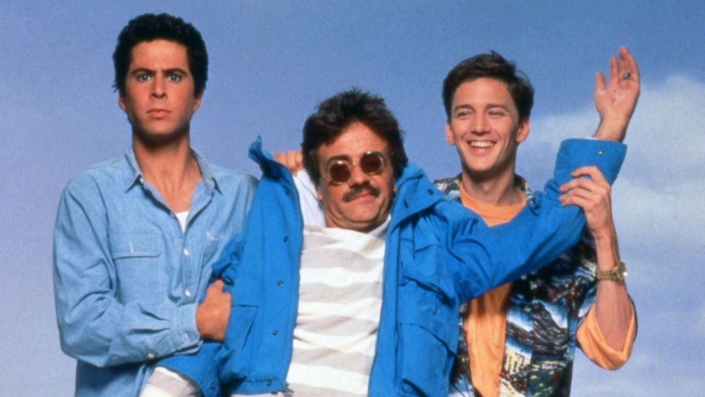 """Screenshot from """"Weekend at Bernies"""" where the living characters are putting Bernie's left arm up as if he was waving. (In case you didn't know, Bernie has ceased to be.)"""