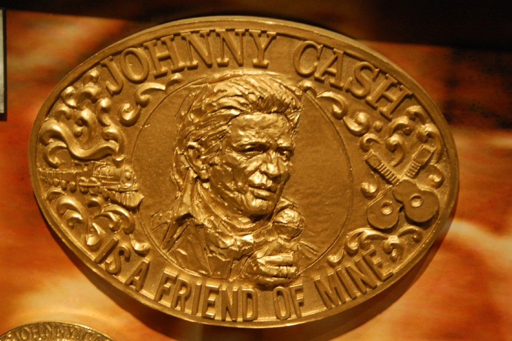 "Golden belt buckle with an image of Johnny Cash's head on it. The words say ""Johnny Cash is a friend of mine"""