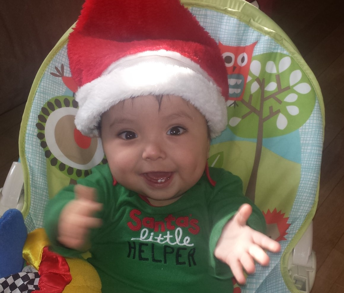 """Baby boy wearing a red Santa hat and a green onesie that says """"Santa's Little Helper."""" He has a huge smile and is clapping his hands together."""