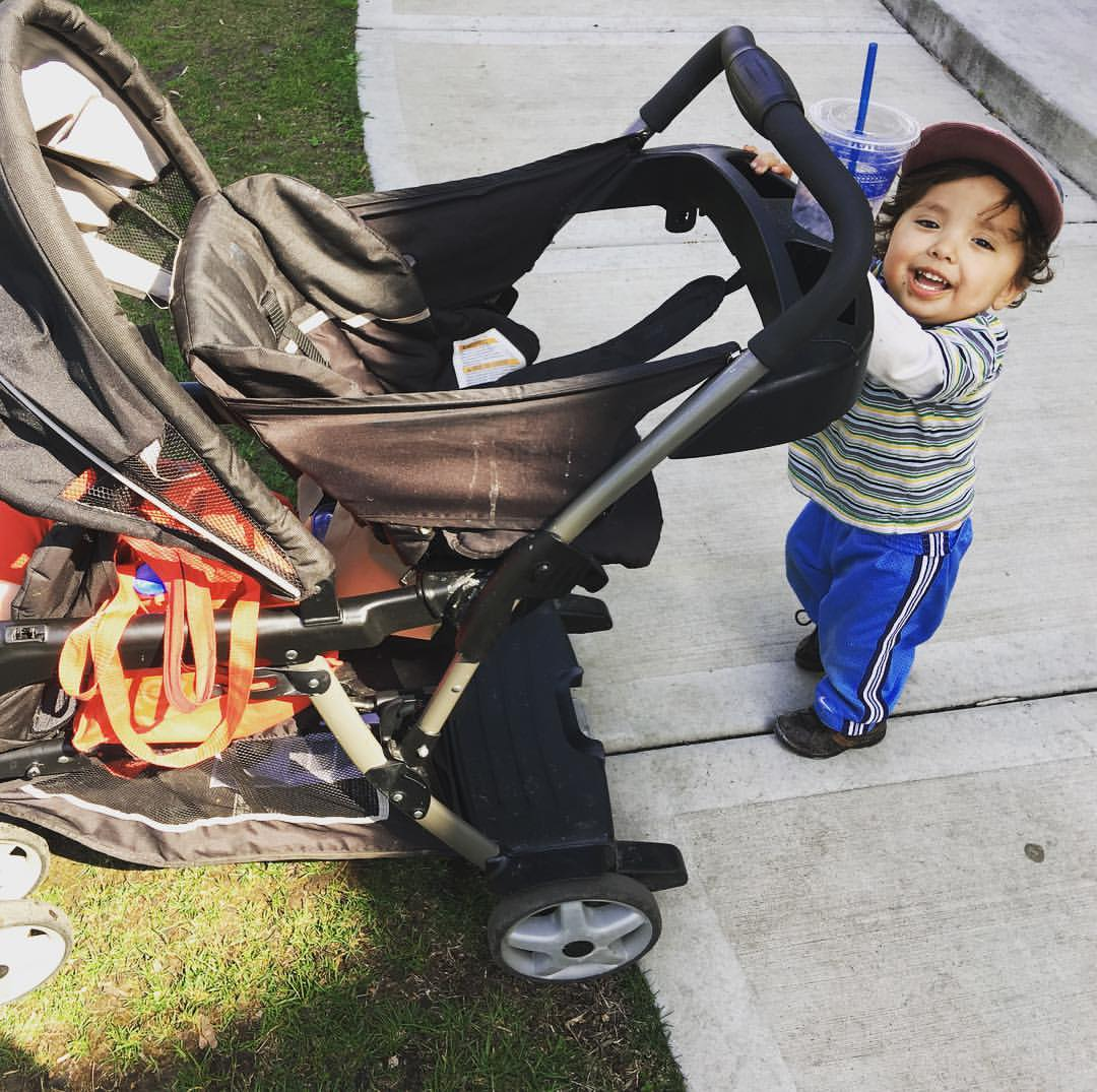 Two year old is pushing a black double stroller off the sidewalk and onto the grass. He looks very happy about it.