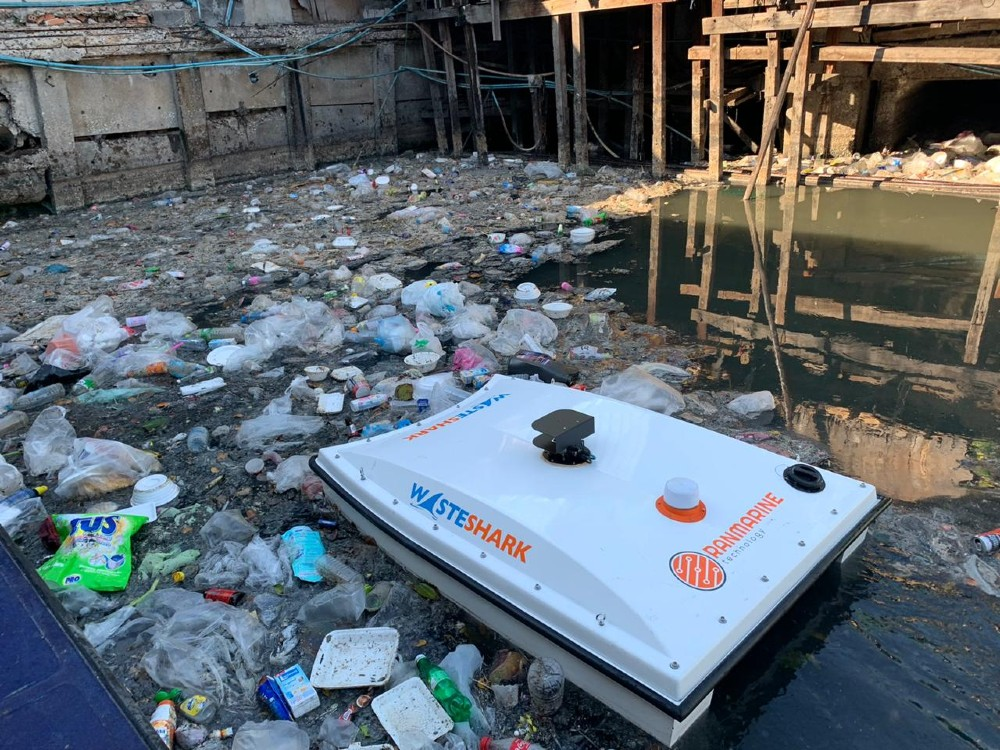 WasteShark, a boxy, light grey swimming drone, cleans up trash in a trash-covered waterway in Thailand.