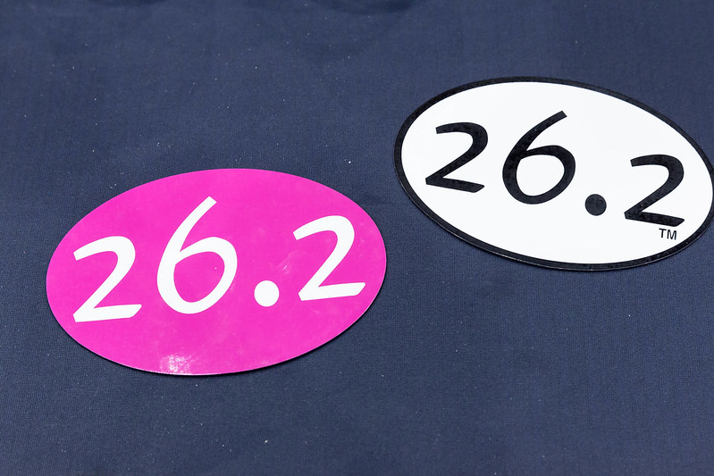 """Two oval bumper stickers that read """"26.2"""" - one is pink with white lettering and the other is white with black lettering. (Photo: 26.2 Miles Sticker by Marco Verch under Creative Commons 2.0 https://foto.wuestenigel.com/26-2-miles-sticker/)"""
