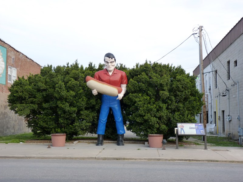 Giant fiberglass statue of a man in a red shirt and blue jeans holding a giant hot dog. (Photo by JymPoiranges via Flickr/Creative Commons https://flic.kr/p/rtLDKX)