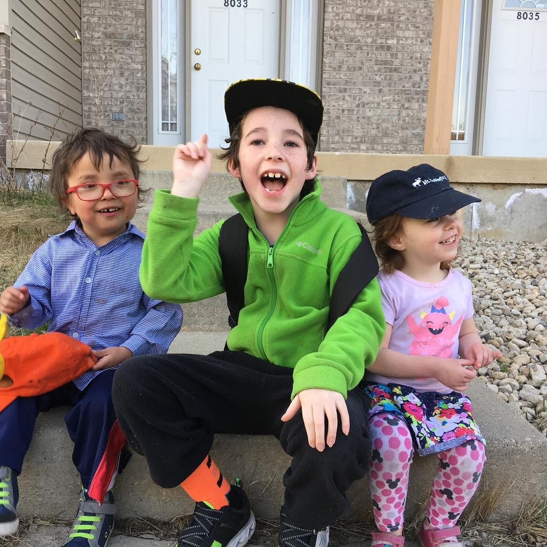 The oldest Carlson kid is telling a joke and gesturing with his right hand. The younger two are smiling and laughing. They're sitting together on a conrete step outside the bus stop.