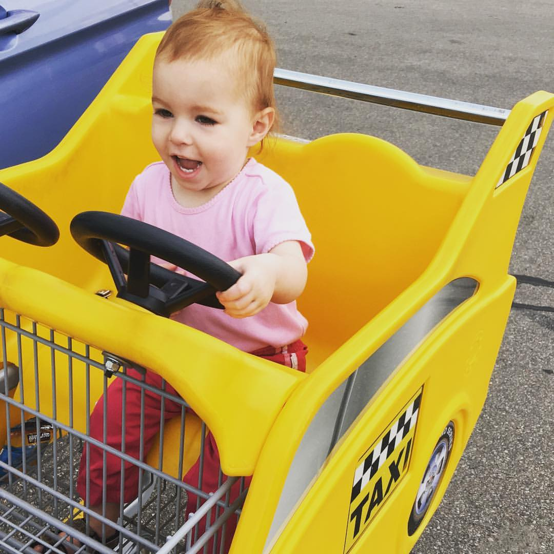 """One year old is giggling as she """"drives"""" a shopping cart that looks like a taxi."""