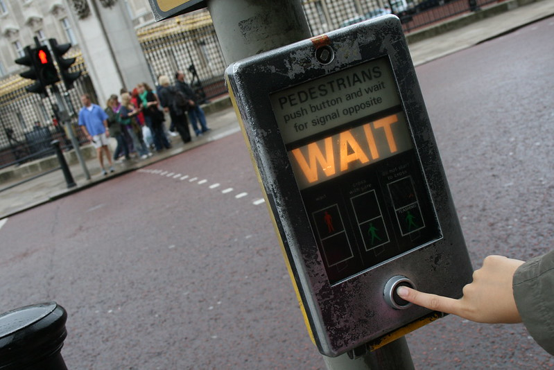 """A hand pushes a button on a crosswalk sign, lit up to say """"WAIT"""" (Photo by mat_n via Flickr/Creative Commons https://flic.kr/p/2pf9kY)"""
