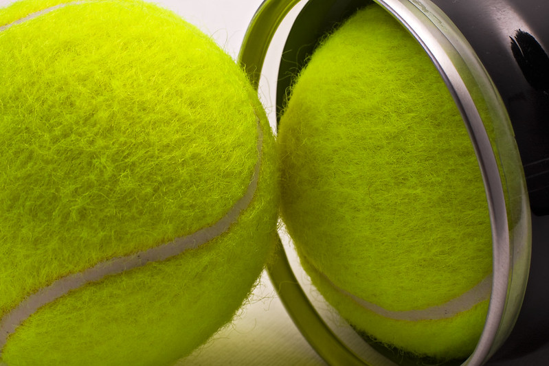 Two tennis balls covered in yellow fluorescent nap and having white curved rubber band. One of the balls is still inside a black plastic container with a shiny metal circular ending. (Photo by Old Photo Profile via Flickr/Creative Commons https://flic.kr/p/7vBa2x)