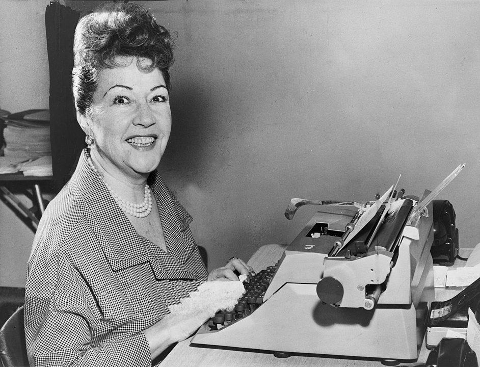 Ethel Merman seated at a typewriter. (Photo by Walter Albertin, derivative work: PawełMM via Wikicommons https://commons.wikimedia.org/w/index.php?curid=14387238)
