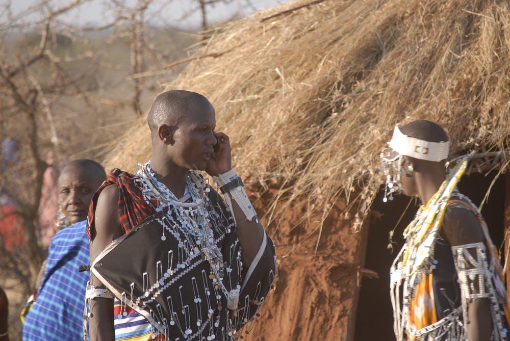 A Maasai man talks on his phone during a community gathering. Timothy D. Baird/Virginia Tech, CC BY-ND
