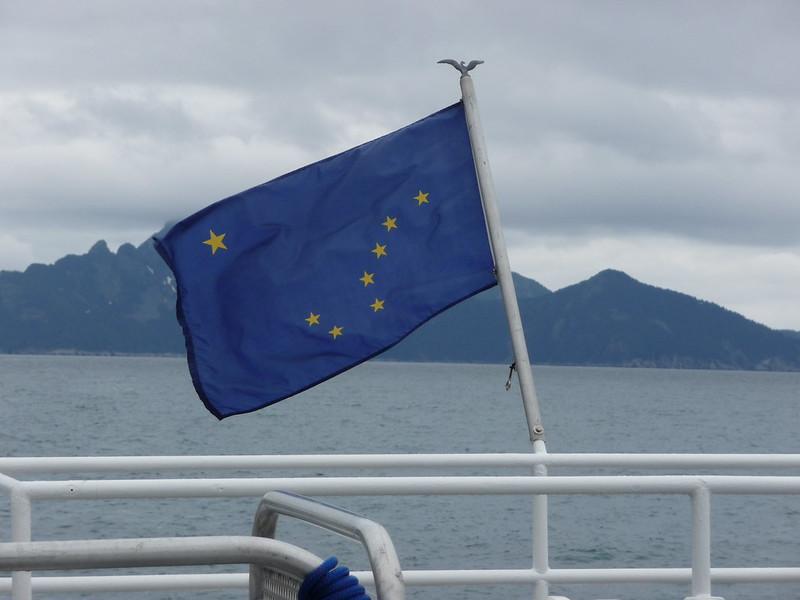Alaska's flag flies off the side of a ship. (Photo by Kim F via Flickr/Creative Commons https://flic.kr/p/7EV3rs)