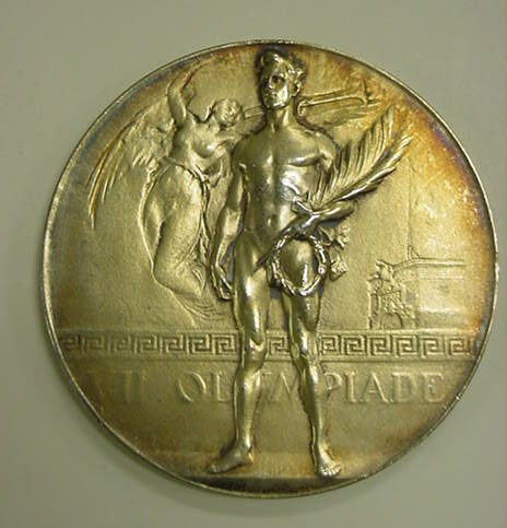 One of four gold medals awarded to Captain Carl T. Osburn at the 1920 Olympics. (Photo by Naval History and Heritage Command from Washington, DC, USA - 2000-158-19 Medal, Olympics, 1920, Antwerp, Gold, Obverse, CC BY 2.0, https://commons.wikimedia.org/w/index.php?curid=40383547)