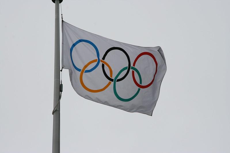 The Olympic flag flies on a pole. (Photo by Ryan Lejbak via Flickr/Creative Commons https://flic.kr/p/RKXqs)