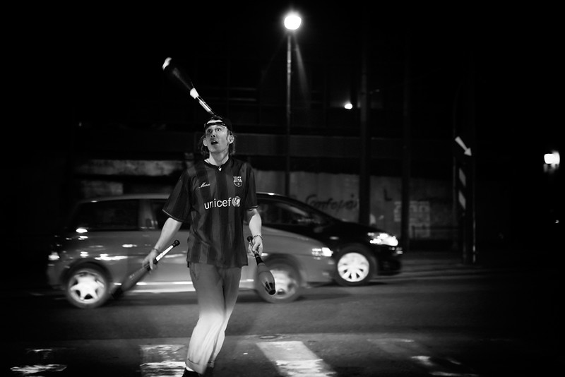 A black and white photo of a guy juggling three clubs next to a street. (Photo by .stefanos papachrisou via Flickr/Creative Commons https://flic.kr/p/8Tpw6N)