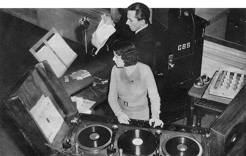 Ora Nichols with assistant George O'Donnell on the set of The March of Time in January 1935. (Photo by Wide World photo for Tower Magazines, Inc. - page 24 Tower Radio, January 1935, Public Domain, via Wikicommons https://commons.wikimedia.org/w/index.php?curid=37427021)