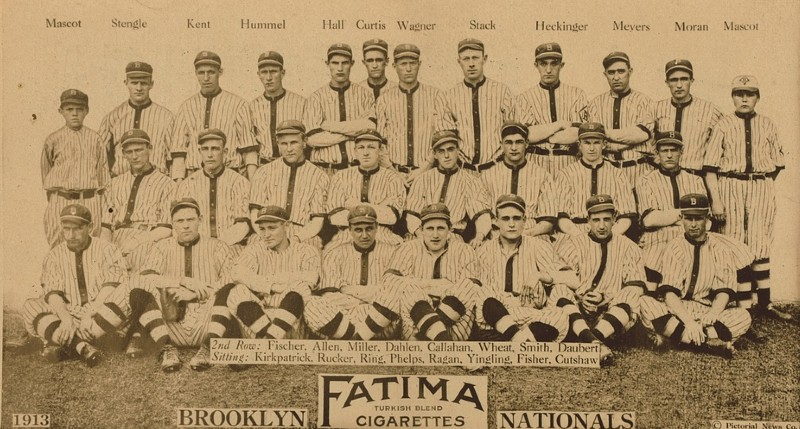 """The Brooklyn Nationals (currently Brooklyn Dodgers) baseball team, with an ad of """"Fatima Cigarettes"""", middle below. Photo via Wikicommons https://commons.wikimedia.org/wiki/Category:Brooklyn_Dodgers#/media/File:Brooklyn_Dodgers_Team_Photograph,_1913.jpg"""