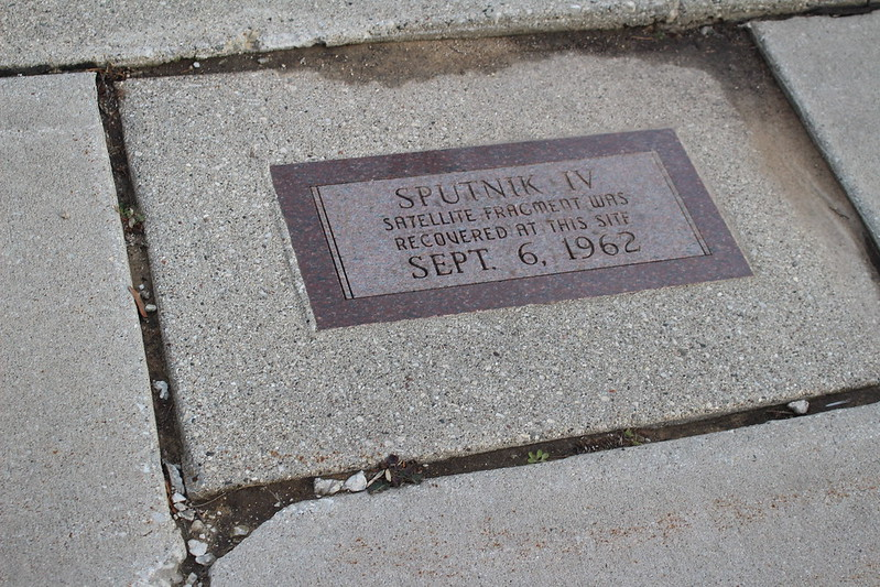 """A metal sign embedded in the sidewalk: """"Sputnik IV satellite fragment was recovered at this site Sept. 6, 1962"""" (Photo by Amy Meredith via Flickr/Creative Commons https://flic.kr/p/Bcz5ec)"""