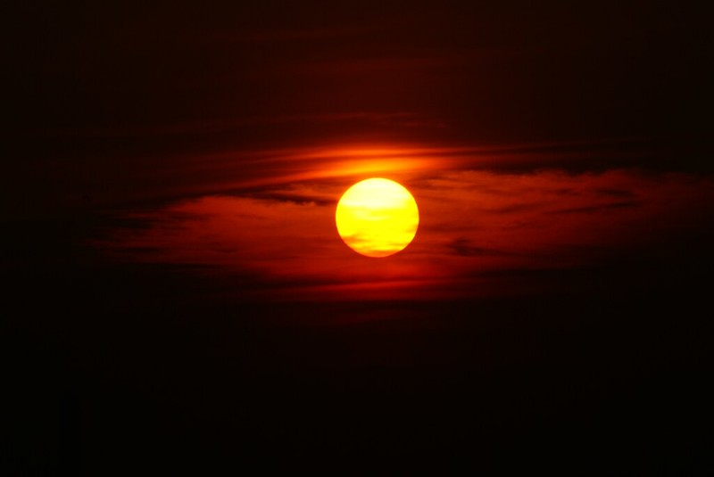A bright orange sun with some clouds moving through. (Photo by Maclej via Flickr/Creative Commons https://flic.kr/p/Cyw2E)