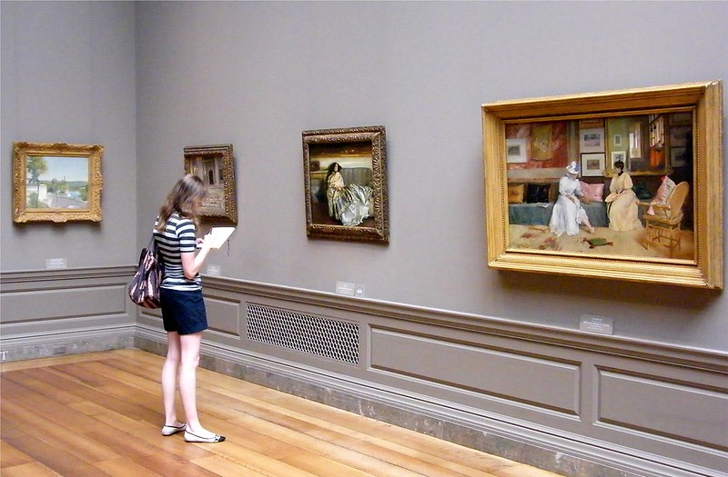 A woman looks at paintings in an art museum. (Photo by Stanley Zimmy via Flickr/Creative Commons https://flic.kr/p/qAtUW8)